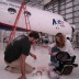 Grad student Bryna Hazelton (2009) and engineer Forest Martinez-McKinney checking parts for the ADELE gamma-ray detector about to be flown above thunderstorms in the NSF/NCAR Gulfstream V jet shown in the back.